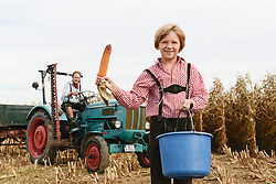 Father and son on tractor in cornfield, Bavaria, Germany