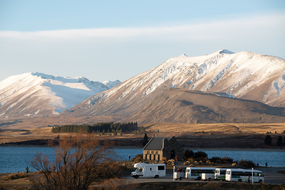 Church of The Good Shepherd overlooking Lake Tekapo with tourists and campervans in the foreground.