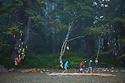 Hikers walk down the beach at Michigan Creek camp, West Coast Trail, British Columbia, Canada.