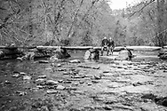 Couple sitting on clapper bridge over the River Barle at Tarr Steps, Exmoor
