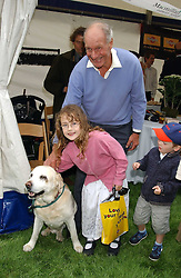 CHARLES PALMER-TOMKINSON, his grandaughter HONOR and their dog at the 3rd annual Macmillan Dog Day in aid of Macmillan Cancer Relief held at Royal Hospital Chelsea, London SW3 on 5th July 2005.<br />