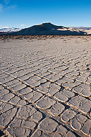 Dried mud flats with Eureka dunes in distance, Death Valley national park, California