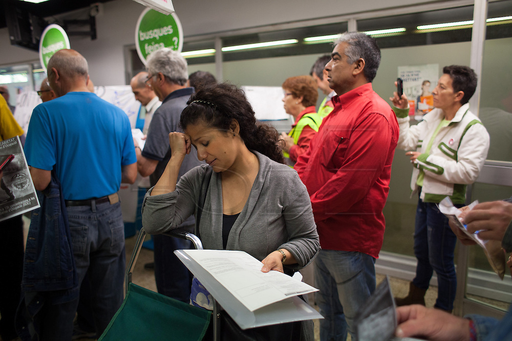 """A woman in the unemployment office of Nou Barris district is waiting to be attended while the office is ocupied by strikers. // Spain's Marchs for Dignity has organized an ocupation of the unemployment offices –INEM- on the eve of May 1st International Worker's Day. With the motto """"bread, work, roof and dignity"""", a total of 400 unemployment offices has been occupied by different movements during two hours (11h to 13h) in the Spanish State. 6 millions of people are unemployed in Spain, many of them don't get the public assistance from the adminitration and others receive the minimum amount of 426€ at a month. 30th April."""