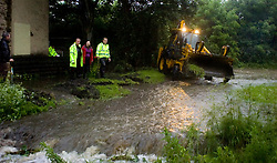 Memories return of June 2007 as heavy rains cause more flooding in Sheffield. Two houses on Ecclesfield Common are threatened by flood waters from over-flowing streams as police officers who have been battling against the flood waters waters with buckets and hand shovels get reenforcements in the shape of a JCB mechanicla digger 09 June 2009 Copyright Paul David Drabble
