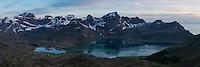 Mountains rise over calm water of Flakstadpollen, Flakstadøy, Lofoten Islands, Norway