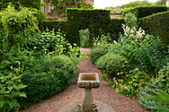 A stone birdbath surrounded by a gravel path and herbaceous borders at Cothay Manor, Greenham, Wellington, Somerset, UK
