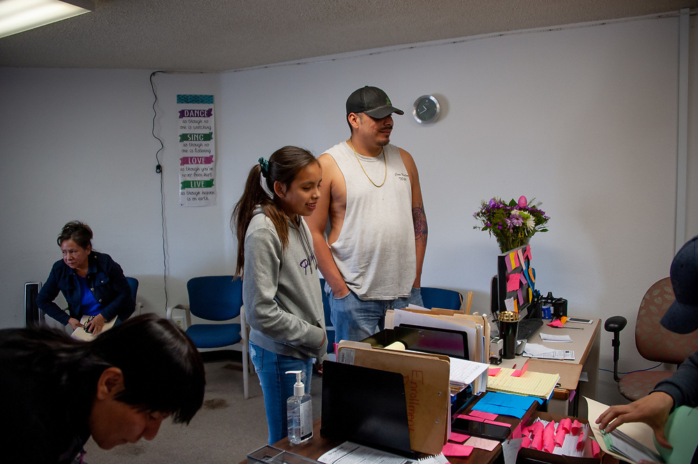 Clayvin Herrera, with his daughter, Twoots,  trying to collect a check for his dividends from coal extraction on the Crow Reservation at the Crow Tribe office of Enrollment & PerCapita in Crow Agency, Montana.