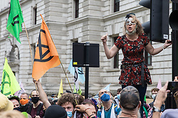 London, UK. 3rd September, 2020. Dr Gail Bradbrook, co-founder of Extinction Rebellion, addresses fellow climate activists at a 'Carnival of Corruption' protest outside the Treasury against the government's facilitation and funding of the fossil fuel industry. Extinction Rebellion activists are attending a series of September Rebellion protests around the UK to call on politicians to back the Climate and Ecological Emergency Bill (CEE Bill) which requires, among other measures, a serious plan to deal with the UK's share of emissions and to halt critical rises in global temperatures and for ordinary people to be involved in future environmental planning by means of a Citizens' Assembly.