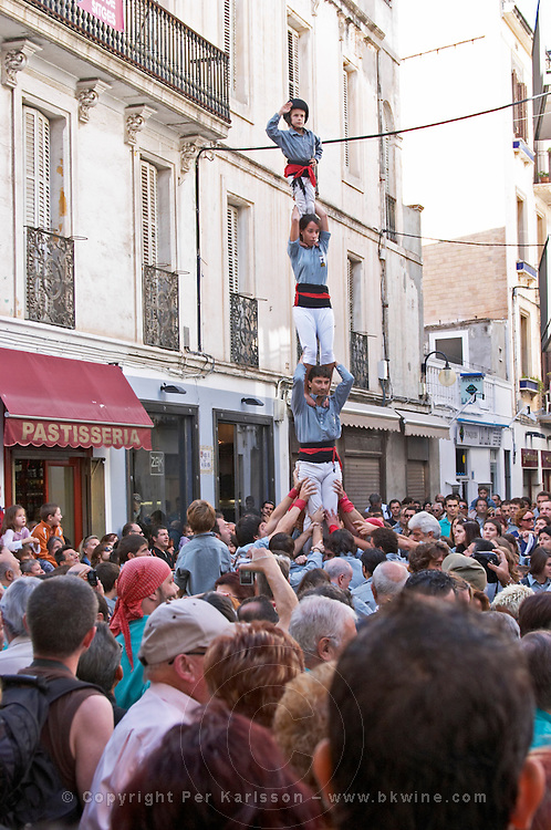 Human tower competition, castellers,  Child on top raises hand: finished. Drawing big crowds. Sitges, Catalonia, Spain