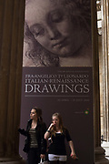 Girls visit a Renaissance art exhibition at London's British Museum. Above them and between pillars is a giant poster called Head of a Woman (1470s) by Andrea del Verrocchio born Andrea di Michele di Francesco de' Cioni, an Italian sculptor, goldsmith  and painter who worked at the court of Lorenzo de' Medici in Florence. His pupils included Leonardo da Vinci, Pietro Perugino and Lorenzo di Credi, but he also influenced Michelangelo. The British Museum's collection of Italian Renaissance drawings is so fragile that its masterpieces are exhibited only once in a generation. About half of the works came from Florence in partnership with the Uffizi and sponsored by BP (British Petroleum). The 100 or so works span the period 1400-1510 by artists including Jacopo and Gentile Bellini, Botticelli, Filippo Lippi, Mantegna, Michelangelo and Raphael.
