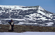 Cross Country Walkers hiking across snowy landscape, blue sky, remote, backpack