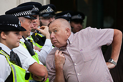 London, UK. 9th June, 2018. A supporter of Tommy Robinson, former leader of the far-right English Defence League, poses in fron t of police officers close to anti-fascists protesting against the March for Tommy Robinson outside Downing Street.