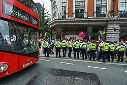 "© Licensed to London News Pictures. 09/09/2020. LONDON, UK.  Police look on as activists from Extinction Rebellion (XR) stage a ""Guerilla Repair"" pop-up outside the H&M store on Oxford Street to protest against the environmental and human effects of fast fashion and disposable fashion.  Photo credit: Stephen Chung/LNP"