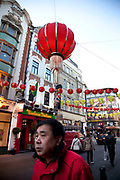 Lanterns decorate the streets on and around Gerrard Street in Chinatown, Soho, London. Chinese New Year will start on January 23rd 2012 and will be the year of the Dragon. Local Chinese community gather on this famous area of central London which is the focus of celebrations. Bright red and yellow lanterns are strung across between the buildings creating a canopy of colour.
