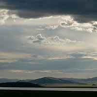 Clouds hang over Lake Erkhel, near Muren, Mongolia.  Ulaan Tolgoi archaeological site is in the background hills.