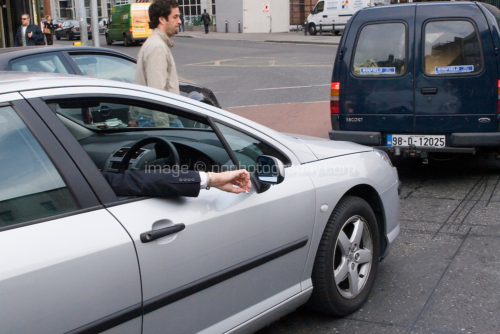 Traffic on the streets in Dublin Ireland, mans arm holding cigarette out car window.