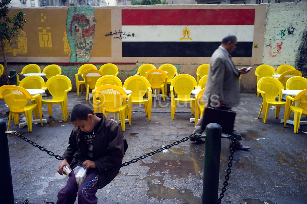 A man checks his telephone as he walks past a street boy that sells tissues for pennies at a pavement cafe in the Bourse area of Cairo with revolutionary graffiti, Cairo, Egypt