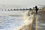 © Licensed to London News Pictures. 30/11/2013. Southwold, UK A woman takes a photograph of waves hitting the sea defences. Crashing waves on the seafront in Southwold, Suffolk today, 30 November 2013. Photo credit : Stephen Simpson/LNP