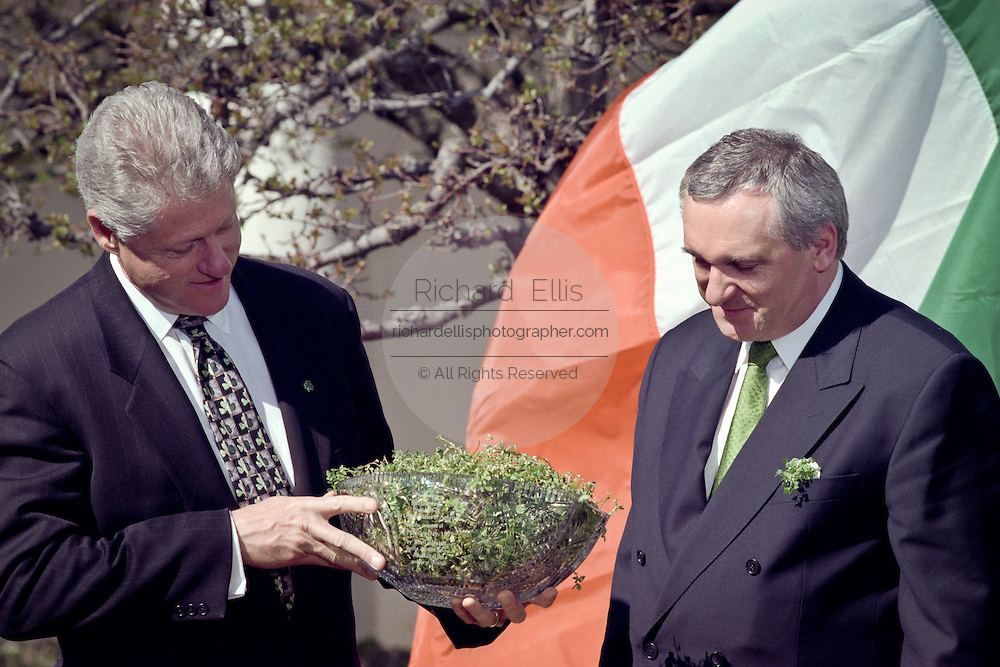 US President Bill Clinton is presented a traditional bowl of shamrocks from Irish Prime Minister Bertie Ahern March 17, 1999 in the Rose Garden of the White House, Washington, DC.