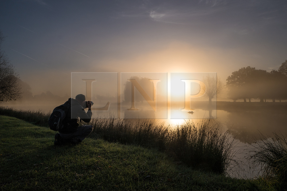 © Licensed to London News Pictures. 30/10/2017. London, UK. A photographer takes a photograph of sunrise in Bushy Park where plummeting overnight temperatures caused the first frost of the winter season. Photo credit: Rob Pinney/LNP