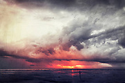 Man standing on Sanur Beach - Bali at sunrise after a thunderstorm