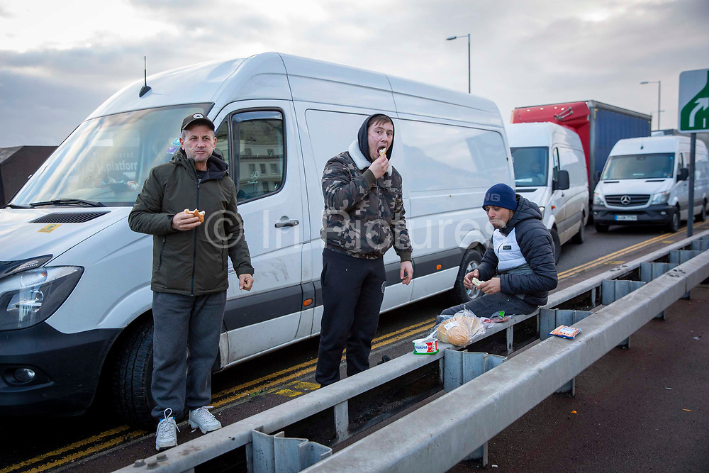 Drivers have their last meal, they have been waiting over 48 hours for the Port of Dover to re-open, on the 23rd of December 2020, Dover, Kent, United Kingdom. The French border was closed due to a new strain of COVID-19 all travellers are now waiting to receive a COVID-19 test before they can board a ferry to Calais, France. Dover is the nearest port to France with just 34 kilometres 21 miles between them. It is one of the busiest ports in the world. As well as freight container ships it is also the main port for P&O and DFDS Seaways ferries.