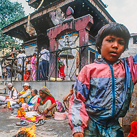 A youngster stands near vendors outside a temple in Kathmandu, Nepal, 1996.