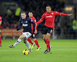 Man Utd Forward Wayne Rooney (ENG) battles for the ball with Cardiff City Forward, Peter Odemwingie (NGA) - Photo mandatory by-line: Joseph Meredith/JMP - Tel: Mobile: 07966 386802 - 24/11/2013 - SPORT - FOOTBALL - Cardiff City Stadium - Cardiff City v Manchester United - Barclays Premier League.