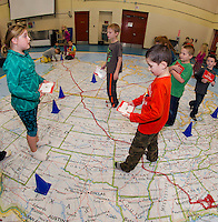 """Belmont Elementary second graders search for """"features"""" such as a Bay, River or Plateau on the interactive map with Phys Ed Teacher Mrs. Nims and Principal Sheila Arnold.  Each class will spend a class period during the two days the map is in Belmont.  (Karen Bobotas/for the Laconia Daily Sun)"""