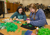 """Amelia Cluett and Kyra Bryant work on a feather head dress during """"Tech Day"""" for Once Upon A Mattress at Belmont High School on Saturday.  (Karen Bobotas/for the Laconia Daily Sun)"""