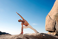 Fit man in yoga pose outdoors on boulders. This particular lunge demonstrates the particular relaxed neck technique developed by Ana Forrest.