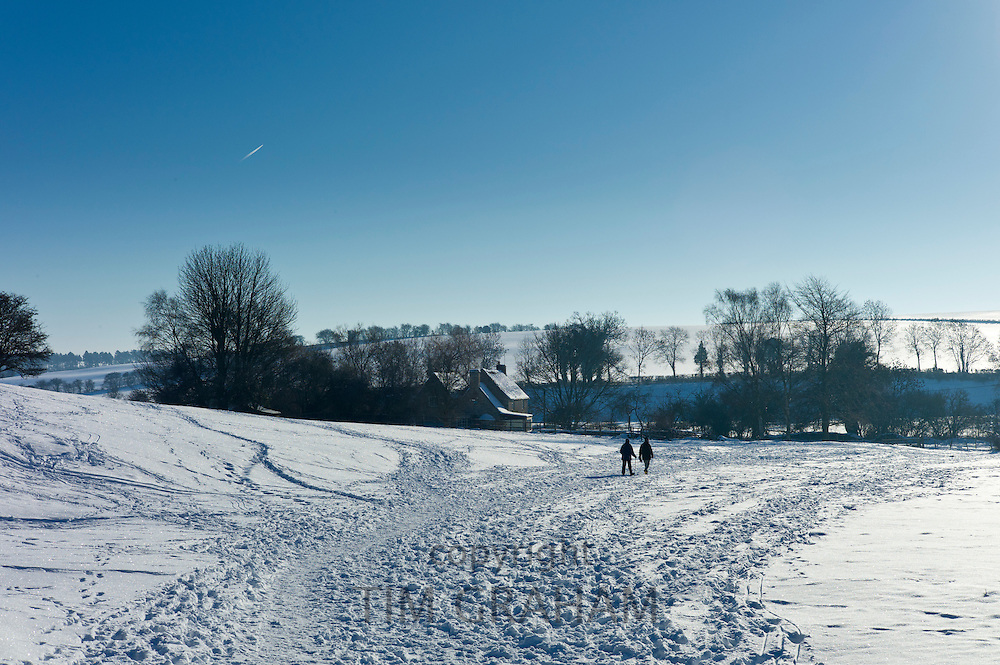Walkers in wintry scene at Widford in The Cotswolds, UK