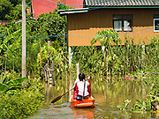 30 SEPTEMBER 2016 - SAI NOI, AYUTTHAYA, THAILAND:  A woman use a boat to go to take her home in Sai Noi, a flooded village on the Chao Phraya River. The Chao Phraya River, the largest river that runs through central Thailand, has hit flood stage in several areas in Ayutthaya and Ang Thong provinces. Villages along the river are flooded and farms are losing their crops due to the flood. This is the same area that was devastated by floods in 2011, but the floods this year are not expected to be as severe. The floods are being fed by water released from upstream dams. The water is being released to make room for heavy rains expected in October.     PHOTO BY JACK KURTZ