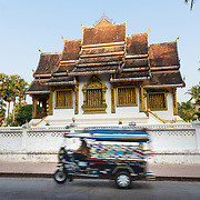 Tuk tuk on street in Luang Prabang with Haw Pha Bang in background