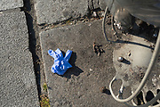 """April, 4th 2020 - Paris, Ile-de-France, France: Masks and gloves thrown away on the sidewalk during the Coronavirus pandemic. Used protection from the spread of the Coronavirus, during the third week of near total lockdown imposed in France. A week after President of France, Emmanuel Macron, said the citizens must stay at home for at least 15 days, that has been extended. He said """"We are at war, a public health war, certainly but we are at war, against an invisible and elusive enemy"""". All journeys outside the home unless justified for essential professional or health reasons are outlawed. Anyone flouting the new regulations is fined. Nigel Dickinson"""
