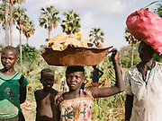 """NUBA MOUNTAINS, SUDAN – JUNE 9, 2018: A group of Nuba stand along the roadside on the way to Hieban.<br /> <br /> In 2011, the government of Sudan expelled all humanitarian groups from the country's Nuba Mountains. Since then, the Antonov aircraft has terrorized the Nuba people, dropping more than 4,080 bombs on hospitals, schools, marketplaces and churches. Today, vestiges of the Antonov riddle the landscapes of daily life, where more than 1 million Nuba live in famine conditions – quietly enduring the humanitarian blockade intended to drive them out of the region. The skies are mostly clear. Yet the collective memory of the bombings remains an open wound, and the Antonov itself a persistent threat. So frequent were the attacks that the Nuba nicknamed the high flying aircraft and its dismal hum: """"Gafal-nia ja,"""" they would declare, running to the hillsides. """"The loss of appetite has come."""""""