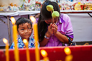 13 APRIL 2013 - BANGKOK, THAILAND:  A woman and her son pray on the plaza in front of Bangkok's City Hall building on the first day of Songkran. Songkran is the traditional Thai New Year's Festival. It is held April 13-16. Many Thais mark the holiday by going to temples and making merit by giving extra alms to monks or offering extra prayers. They also mark Songkran with joyous water fights. Songkran has been a national holiday since 1940, when Thailand moved the first day of the year to January 1.   PHOTO BY JACK KURTZ