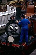 An engineer polishes a Thomas the Tank Engine locomotive whilst in sidings on the Bluebell Railway at Kingscote, England. The Bluebell Railway is a heritage line running for nine miles along the border between East and West Sussex, England. Steam trains are operated between Sheffield Park and Kingscote, with an intermediate station at Horsted Keynes. The railway is managed and run largely by volunteers. It has the largest collection (over 30) of steam locomotives in the UK, the first preserved standard gauge steam-operated passenger railway in the world to operate a public service, running its first train on 7 August 1960.