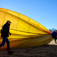 120613       Cable Hoover<br /> <br /> Pilot Jeff Johnson, left, and his crew rush to pack up their balloon as rising winds force them to cancel their launch during the Red Rock Balloon Rally at Red Rock Park in Gallup Friday.