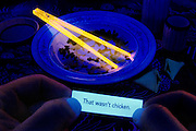 A fortune cookie informs a restaurant customer that the meal just consumed wasn't chicken.Black light