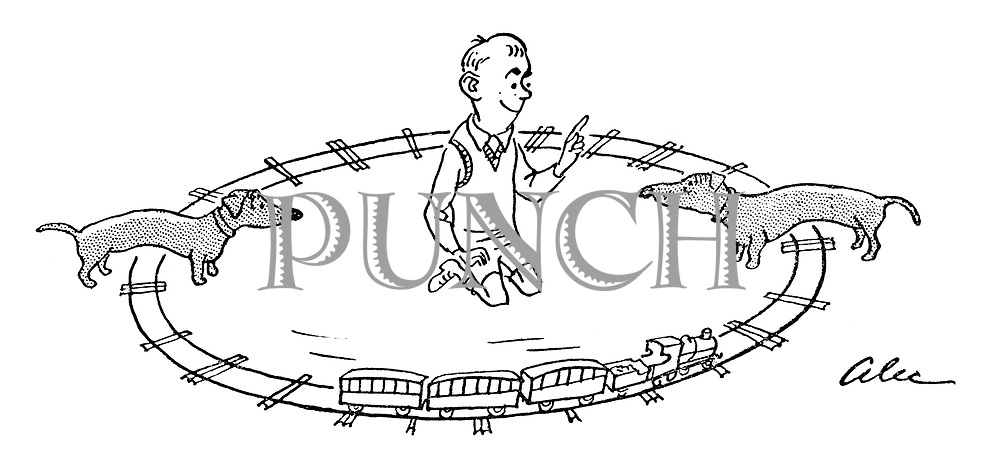 (A boy gets his two Dachshunds to act as bridges for his toy train set)
