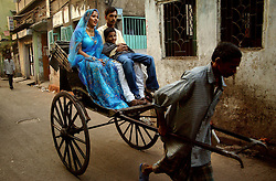 """The hand rickshaw that was brought to Kolkata, formerly known under the British regime as Calcutta, India in 1900 by Chinese immigrants is being banned at the beginning of 2006. The city government want s to attract foreign investment and they say the hand-rickshaw """"wallahs"""" create an uncomfortable image of the city.  The pullers themselves do not have any ethical problems with pulling another man and justify their trade by saying thar rickshaws provide affordable transportation for the poor, do not pollute the environment and provide a desperately needed source of income.  The hand rickshaw is one of the oldest vehicles in the city and there are an estimated 18,000 rickshaw pullers who will be put out of work with no other possibilities. Most of the pullers live in the streets with their families or in a community shelter, a """"dera"""" with 20-25 other pullers. Most pullers make less than $2 per day but end up spending most of it on rent for the rickshaw, bribes to policemen and food. (Ami Vitale/Getty Images)"""