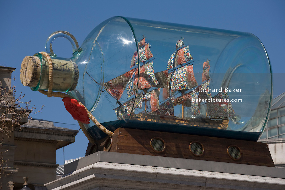 """Artist Yinka Shonibare's artwork Nelson's Ship in a Bottle on Fourth PLinth London's in Trafalgar Square. Shonibare said his version of HMS Victory with its textile sails with African and batik prints reflects the multicultural and diverse capital. The 2.35m high ship inside a specially-made glass bottle, which is a 1:29 scale replica of the original HMS Victory, will be in place for 18 months. 37 large sails are made of patterns which are commonly associated with African dress and culture. The patterns also look back at the path of colonialism as the patterns were inspired by Indonesian batik design, which were mass produced by the Dutch and sold to the colonies in West Africa. Turner Prize-nominated Shonibare said: """"For me its a celebration of London's immense ethnic wealth."""
