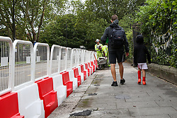 © Licensed to London News Pictures. 29/08/2020. London, UK. A child and his father walk past the barriers which are erected for social distancing at the entrance of Chestnuts Primary School in Tottenham, north London, as the school prepares for reopening next week, at the start of the new academic year. The council and the school are putting in place measures for social distancing and safe conditions following the coronavirus pandemic. <br /> <br /> ***Permission Granted***<br /> <br /> Photo credit: Dinendra Haria/LNP