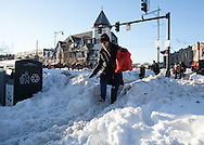 Brookline, MA 02/10/2013<br /> A pedestrian makes her way over a steep snow bank in Coolidge Corner on Sunday afternoon.