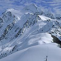 Skiers hike up Shuksan Arm, by Washington's Mount Baker Ski Area, for powder skiing below dramatic Mount Shuksan.