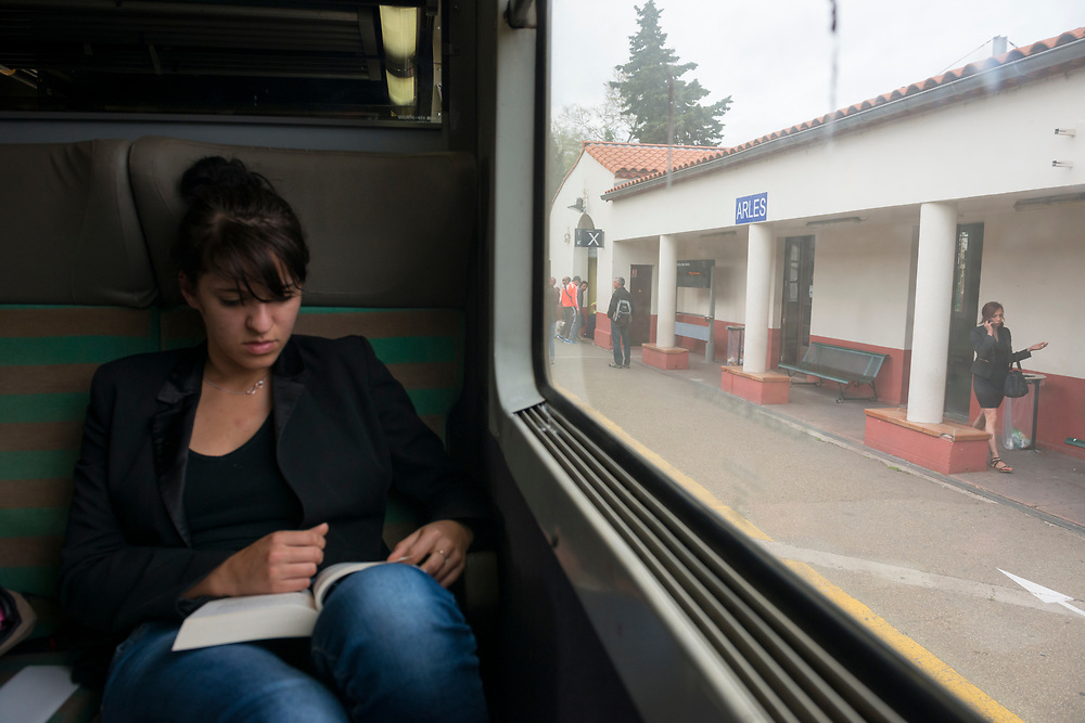 A young woman on a train traveling from Avignon to Marseille, in southern France, reads a book during a brief station stop in Arles.