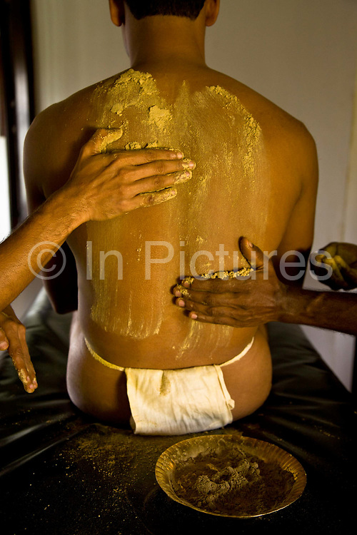 A patient receives a four handed massage also known as udvarthanam treatment as part of the overall Ayurveda experience. This treatment aims to reduce fat, by draining fat carrying lymphatic fliud from the body, improving metabolism, and accumulation of cellulite, Kalari Kovalikom, Kerala, India.