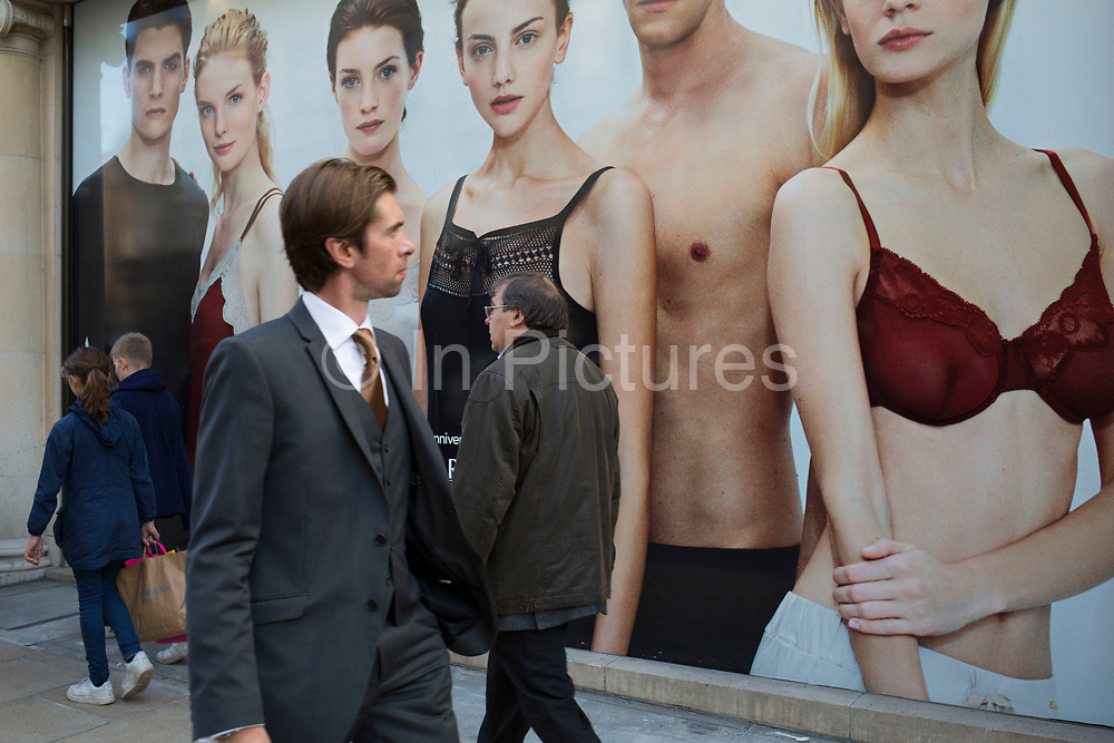 Hoarding outside a shop under refurbishment makes an interesting street scene on New Bond Street, London, UK. A weird visual juxtaposition is created as people integrate with the large scale printed photograph. Man looks at a woman in an underwear advertising picture.