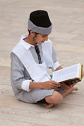 Middle East, Israel, Jerusalem, boy in Bar Mitzvah ceremony  sitting with prayer book in plaza near Western Wall